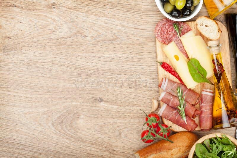 Formaggio, prosciutto di Parma, pane, verdure e spezie immagine stock