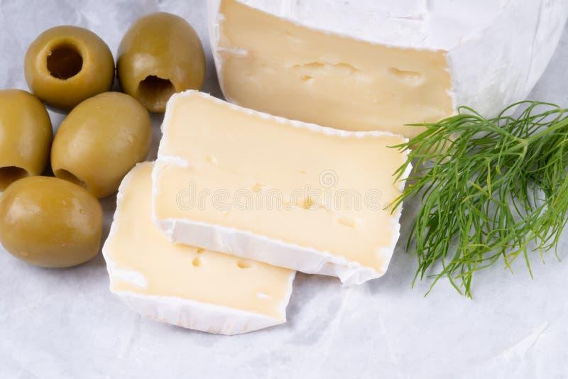 Formaggio puzzolente affettato del camembert con le olive su una tavola rustica di legno fotografie stock libere da diritti