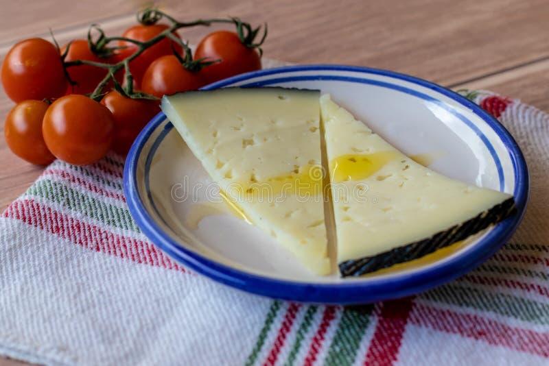Formaggio saporito del latte della mucca con olio d'oliva ed i pomodori ciliegia sul piatto ceramico immagini stock libere da diritti