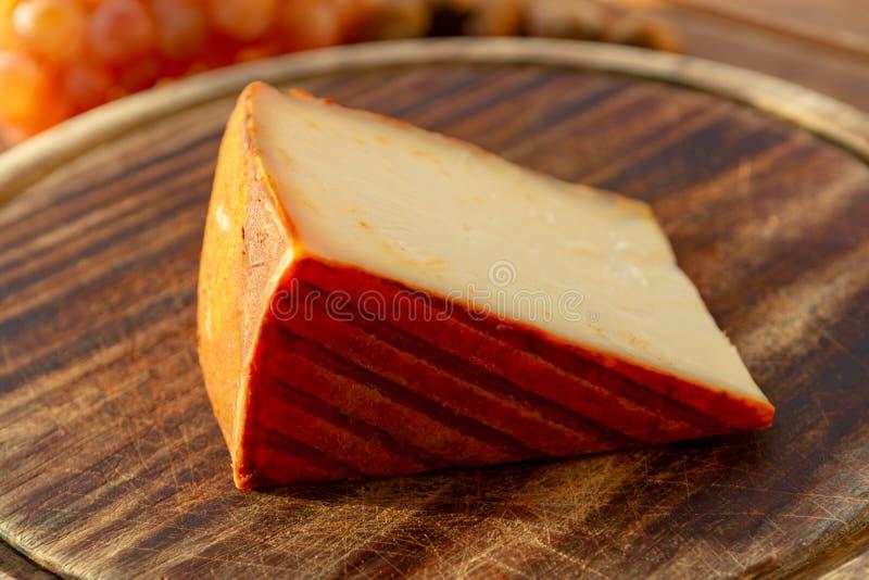 Formaggio spagnolo del latte di capra con il rivestimento della paprica e le uve da tavola rosa mature fotografia stock libera da diritti