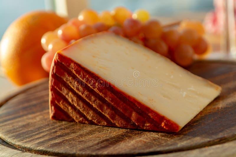 Formaggio spagnolo del latte di capra con il rivestimento della paprica e le uve da tavola rosa mature immagine stock