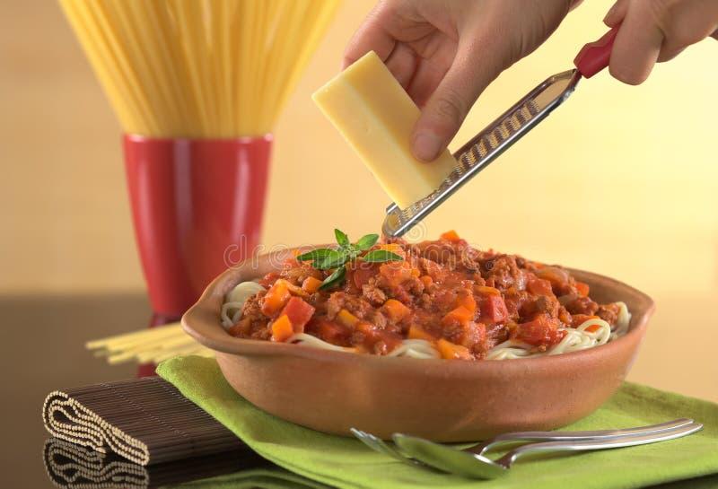 Formaggio stridente sopra spaghetti Bolognaise fotografia stock