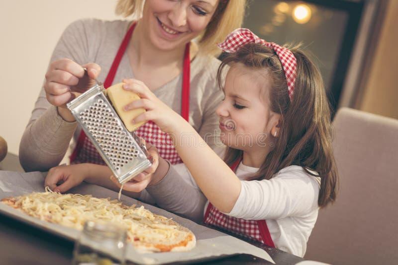 Formaggio stridente sulla pizza fotografia stock