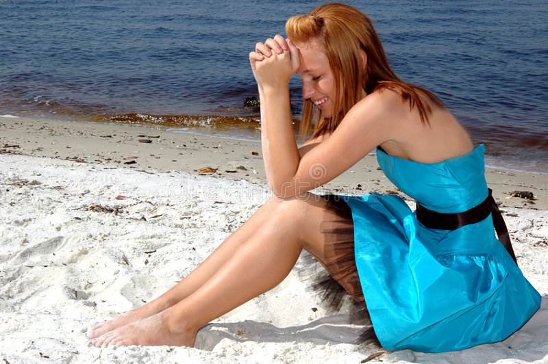 Formal on the beach. A pretty teen sitting in the sand on the beach in a formal dress royalty free stock image