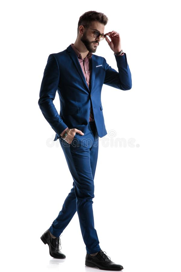 Formal businessman walking with hand in pocket fixing glasses stock photo