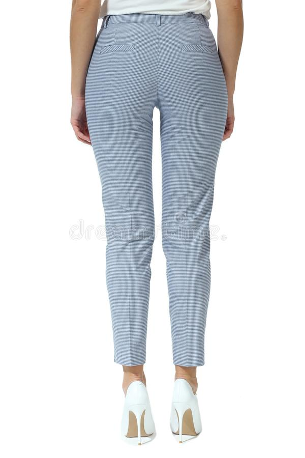 Checked trousers with stripes on model legs with white stiletto heels. Formal checked trousers with stripes on model legs with white stiletto heels stock image