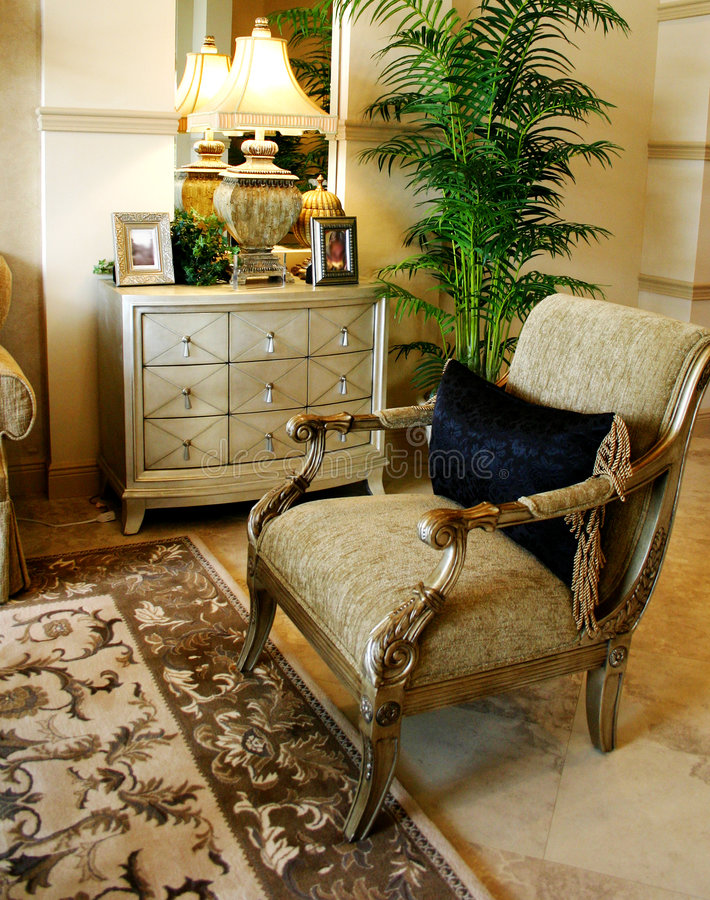 Formal Corner. Of living room with comfortable chair, chest of drawers, lamp, floral carpet, and palm tree