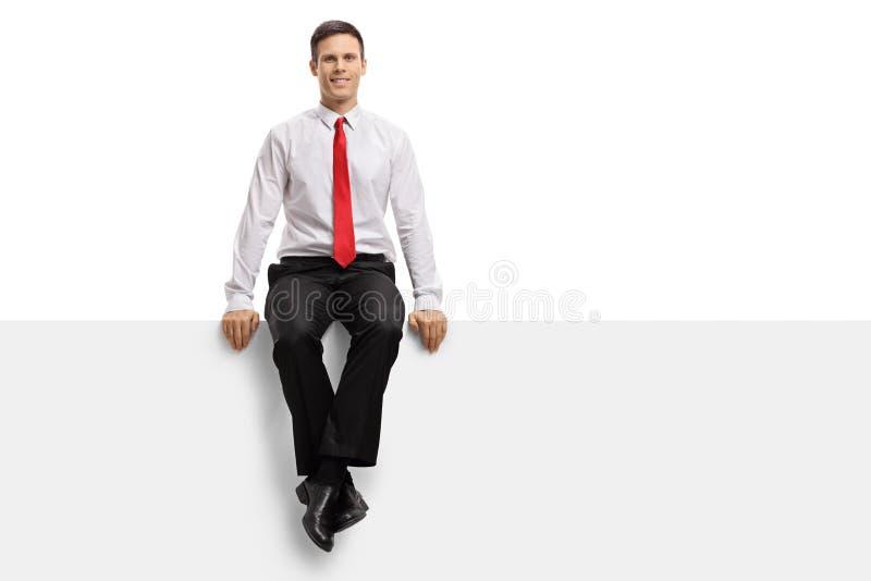 Formal gekleideter Kerl, der auf einer Platte sitzt stockfotografie