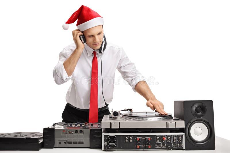 Formal gekleideter Kerl, der einen Weihnachtshut trägt und Musik spielt lizenzfreies stockbild