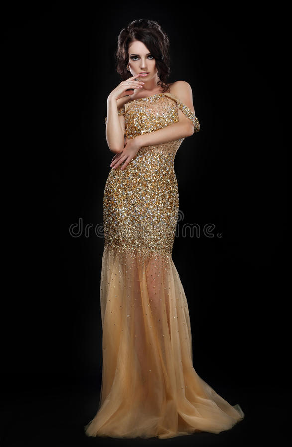 Formal Party. Glamorous Fashion Model in Elegant Golden Dress over Black. Formal Party. Fashion Model in Elegant Golden Dress over Black stock photo