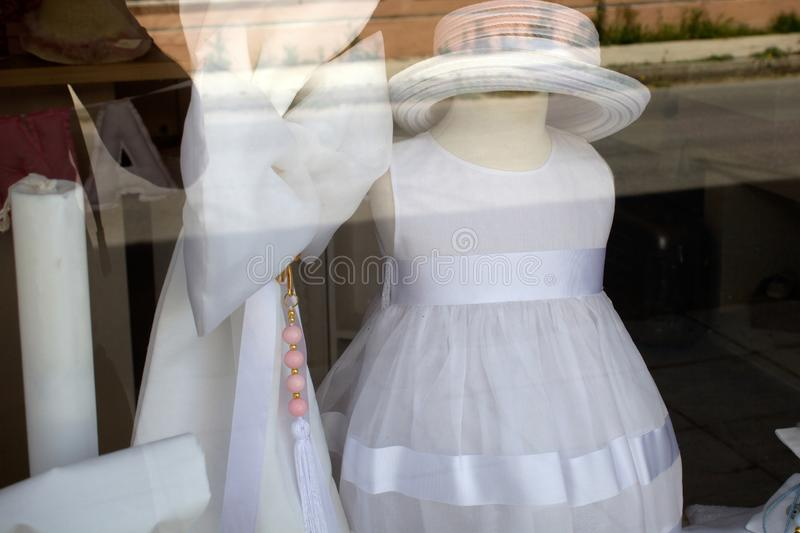 Formal Wear and Accessories for Kids on Special Occasions. Cocktail Dress and Straw Hat on Display Window. White Tulle royalty free stock photography