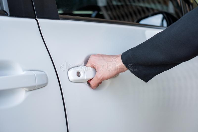 Formale Hand auf dem Griff, der eine Autotür öffnet stockbild