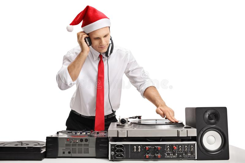 Formally dressed guy wearing a christmas hat and playing music royalty free stock image