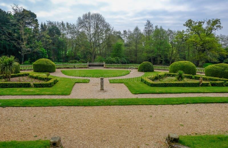 Formalny zapadnięty ogród z kształtnymi krzakami, żywopłoty, łóżka i ścieżki z zielonymi ścieżkami, gazonu i żwiru obraz stock