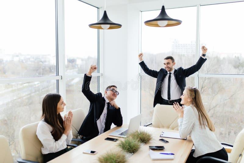 formalwear的商人庆祝胜利,当一起坐在桌上时 免版税库存图片
