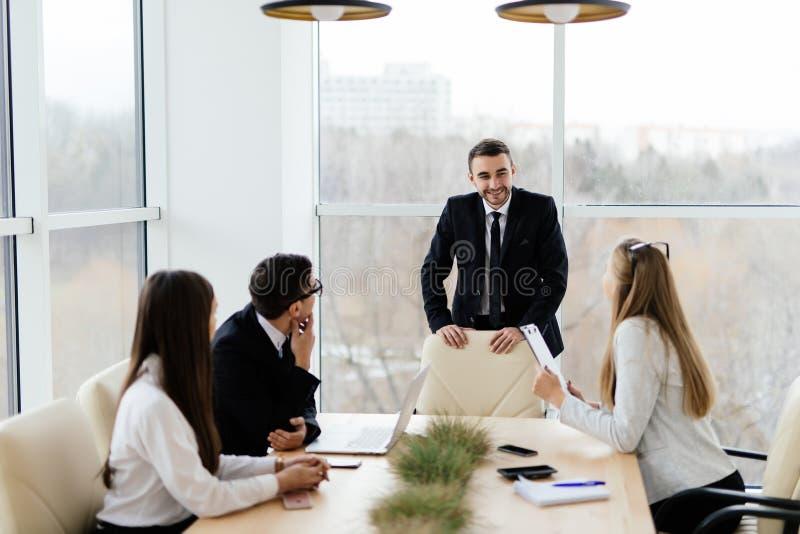 formalwear的商人谈论与领导某事,当一起坐在桌上时 免版税库存图片