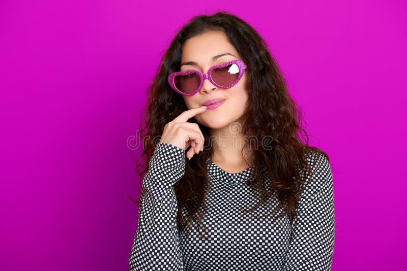 Formar den härliga ståenden för den unga kvinnan som poserar på purpurfärgad bakgrund, långt lockigt hår, solglasögon i hjärta, g arkivfoto