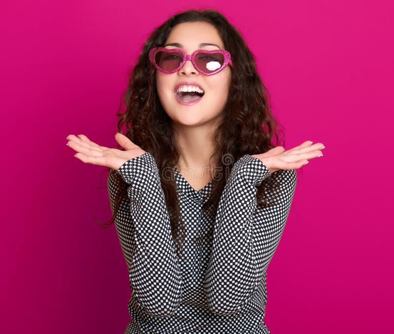 Formar den härliga ståenden för den unga kvinnan som poserar på rosa bakgrund, långt lockigt hår, solglasögon i hjärta, glamourbe royaltyfri foto