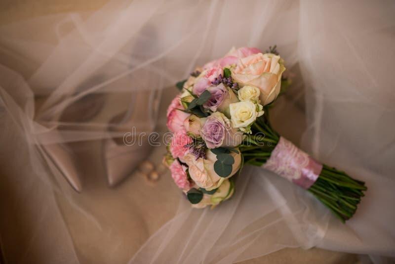 Formas clásicas del ramo nupcial delicado de la boda en tonos en colores pastel con las rosas El casarse floristry Zapatos nupcia fotografía de archivo
