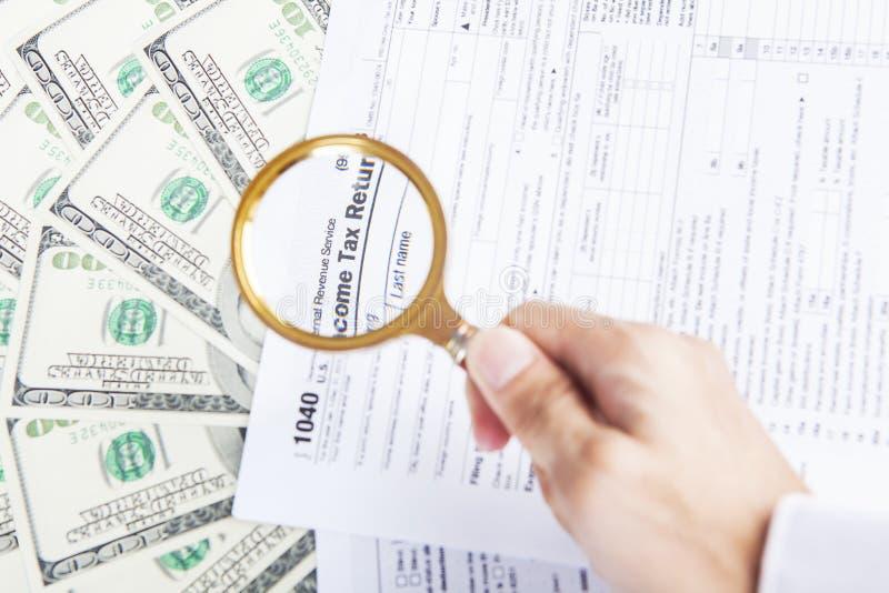 Formas de impuesto y dinero del dólar debajo de la lupa fotografía de archivo