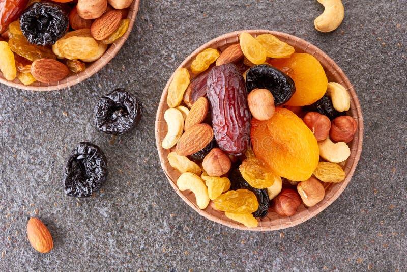 Formas de papel con la mezcla de frutas y de nueces secadas sobre el fondo de piedra imagen de archivo libre de regalías