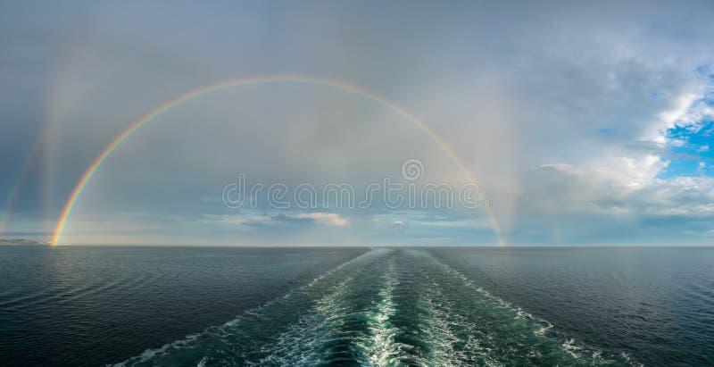 Formas dobles dramáticas del arco iris sobre la estela de un barco de cruceros en el mar fotografía de archivo