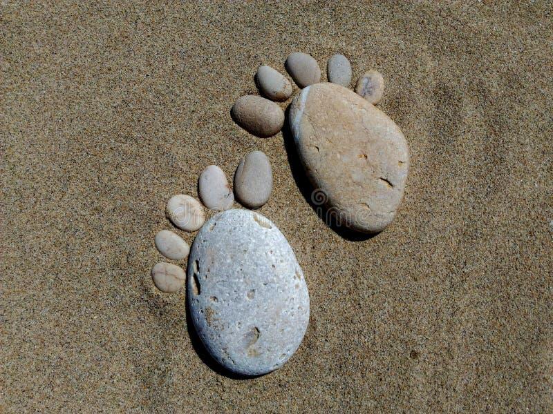 Formas dos pés, seixos no mar fotos de stock royalty free