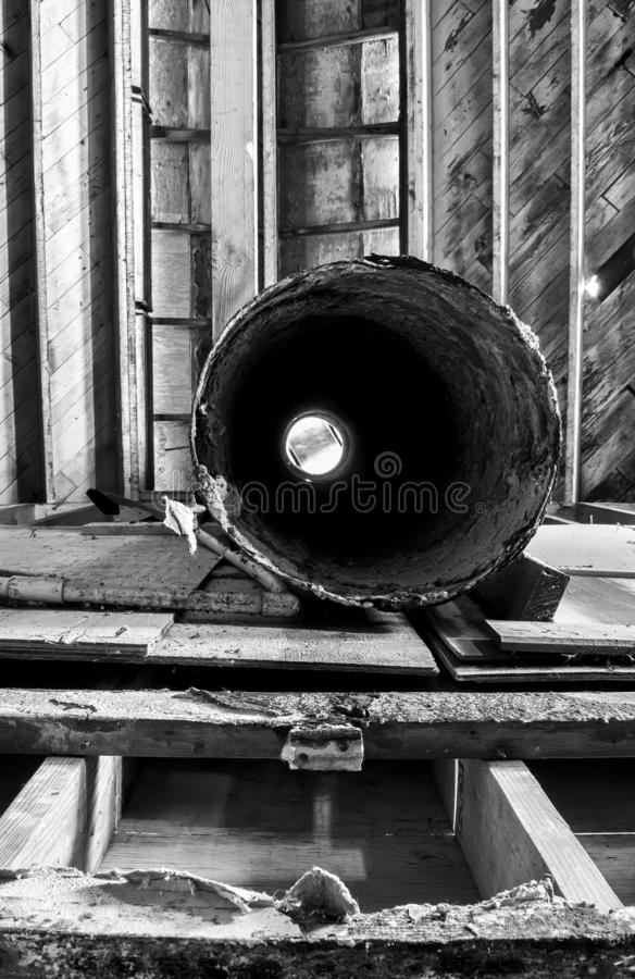 Formas e texturas preto e branco na tubulação circular do ferro e no teto de madeira do armazém industrial abandonado fotografia de stock royalty free