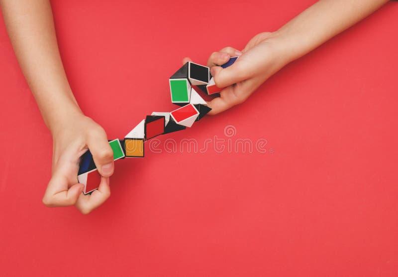Formas mágicas coloridas do enigma da torção da régua da serpente nas mãos das crianças no fundo vermelho fotografia de stock