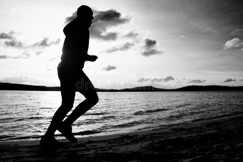 Formation au coucher du soleil Homme grand courant Une silhouette de taqueur au chemin le long du littoral de lac photographie stock libre de droits