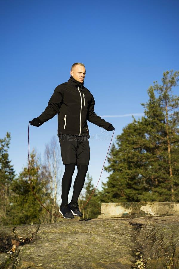 Formation caucasienne masculine de boxeur de Moyen Âge et corde à sauter dehors en nature photo stock