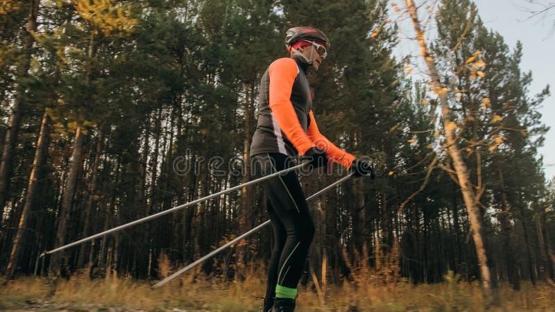 Formation d'un athlète sur les patineurs de rouleau Tour de biathlon sur les skis de rouleau avec des poteaux de ski, dans le cas photographie stock libre de droits
