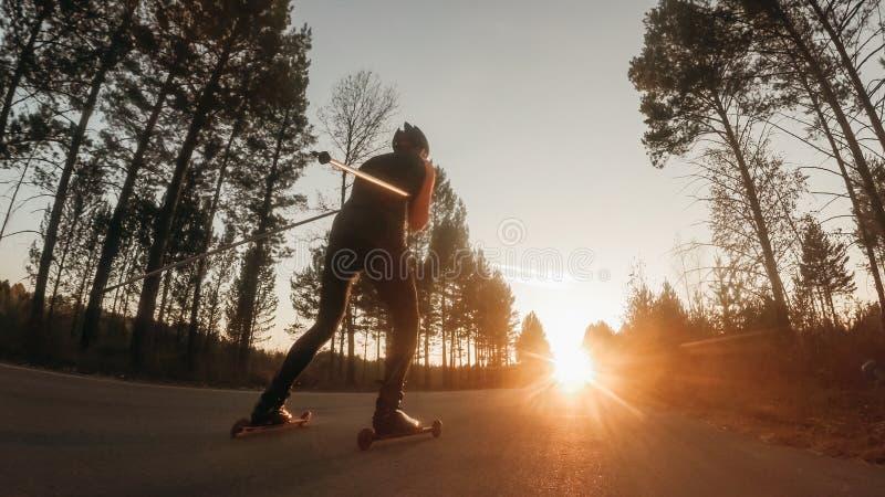 Formation d'un athlète sur les patineurs de rouleau Tour de biathlon sur les skis de rouleau avec des poteaux de ski, dans le cas photos stock