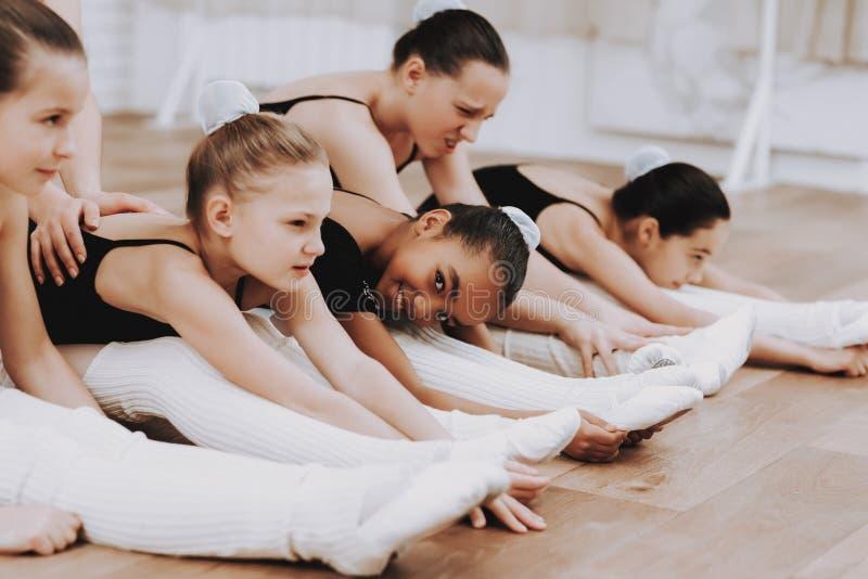 Formation de ballet des filles sur le plancher avec le professeur photographie stock