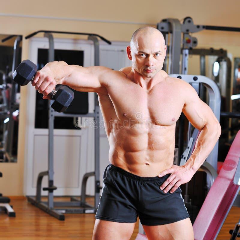 Formation de Bodybuilder avec l'haltère à disposition images stock