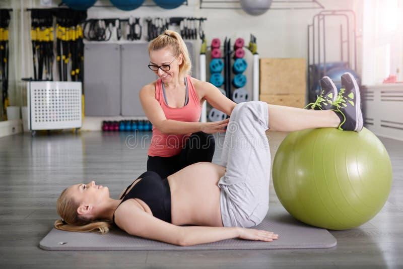Formation de femme enceinte avec l'entraîneur avec la boule de pilates photographie stock