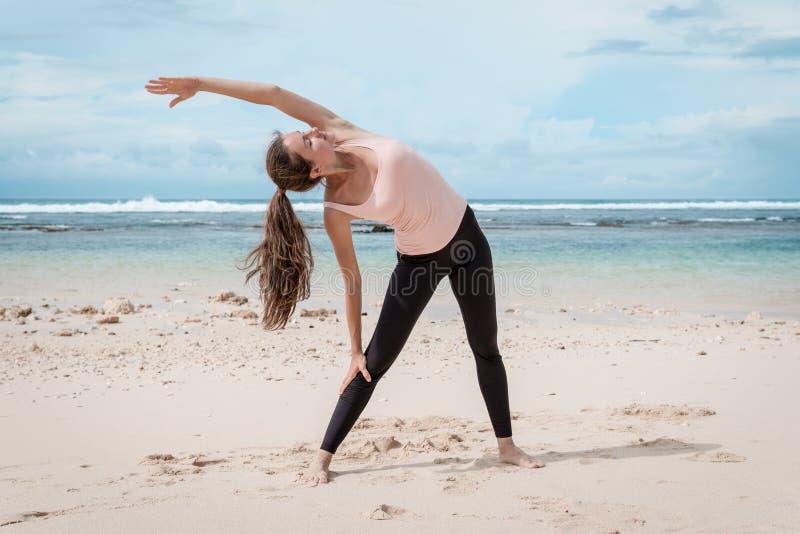 Formation de femme sur la plage devant la mer Matin gymnastique Concept actif sain de mode de vie image libre de droits