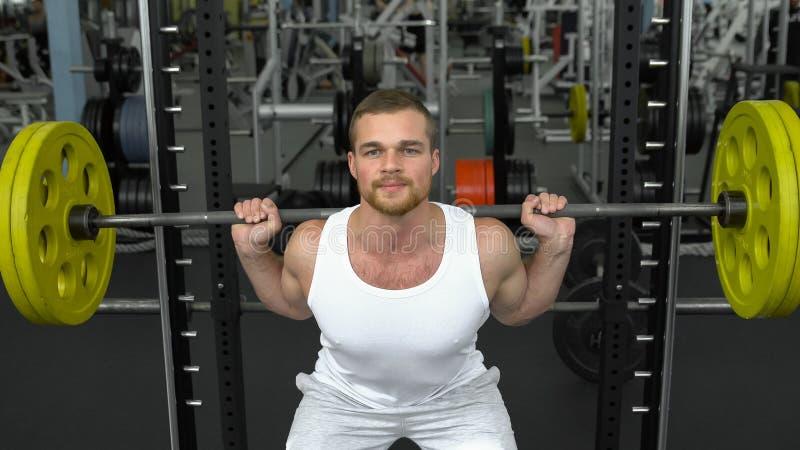 Formation de force dans le gymnase type dans le T-shirt faisant des postures accroupies avec un barbell bodybuilder faisant l'exe images stock