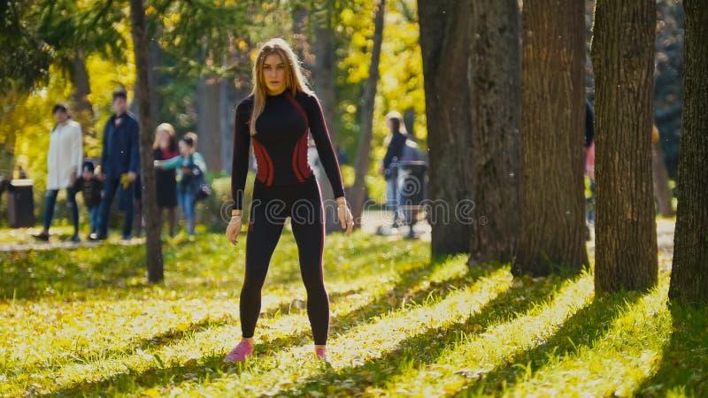 Formation de force de femme de forme physique faisant la séance d'entraînement au parc ensoleillé d'automne Fille sportive caucas photographie stock