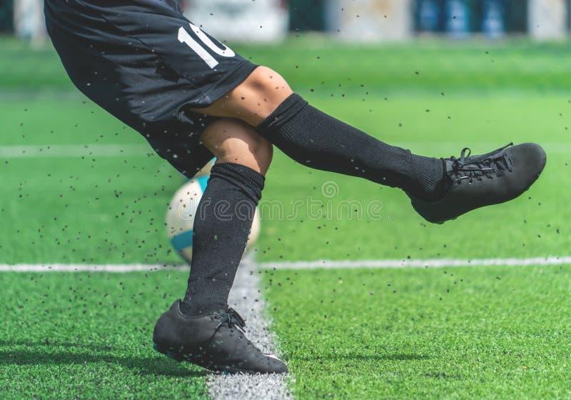Formation de garçon du football donnant un coup de pied la boule dans le domaine de formation du football photographie stock