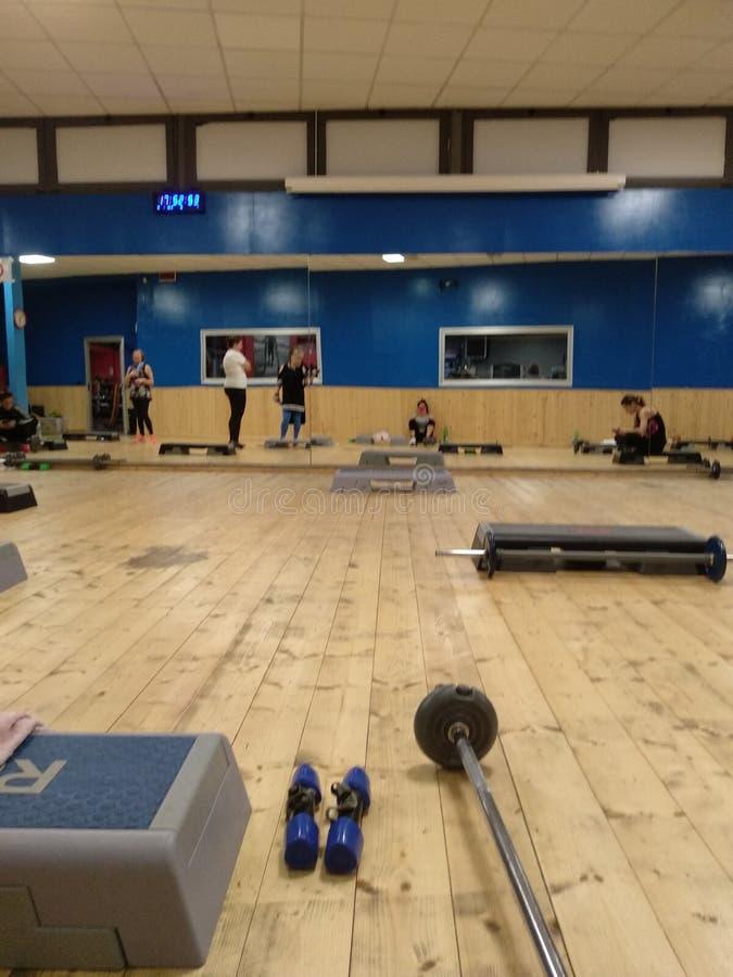 Formation de gymnase gymnastique pour le corps avec des poids, des étapes et d'autres outils photographie stock