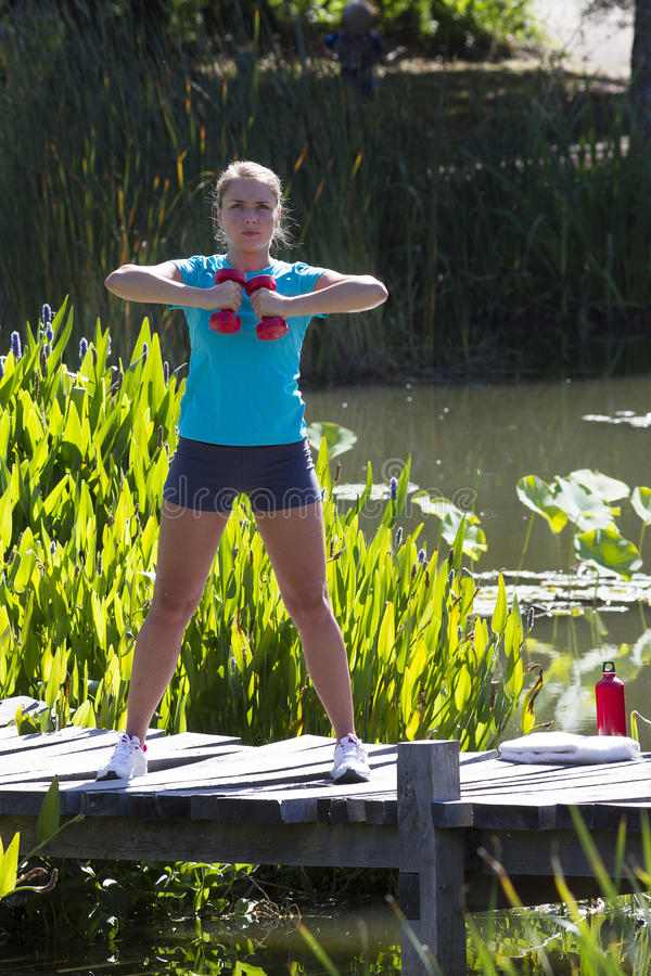Formation de jeune femme avec des haltères sur le pont en bois et l'eau photo libre de droits