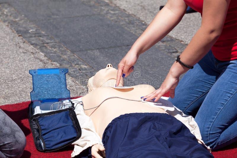 Formation de premiers secours en utilisant le dispositif externe automatisé de défibrillateur - AED photographie stock