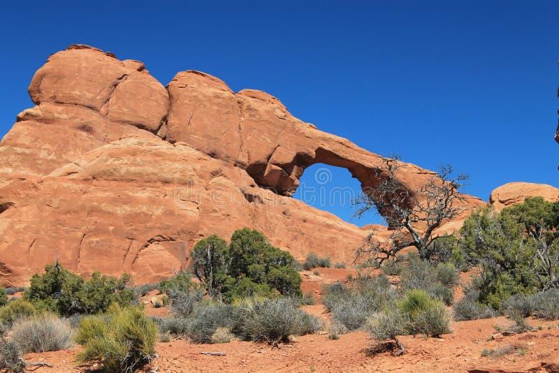 Formation de roche d'arc sous les nuages bleus pendant la journée photographie stock libre de droits