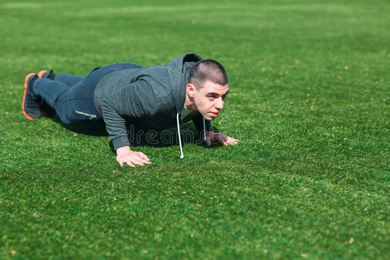 Formation de s?ance d'entra?nement de planche d'homme de forme physique en parc dehors Le jeune type fait l'exercice Mode de vie  photos stock
