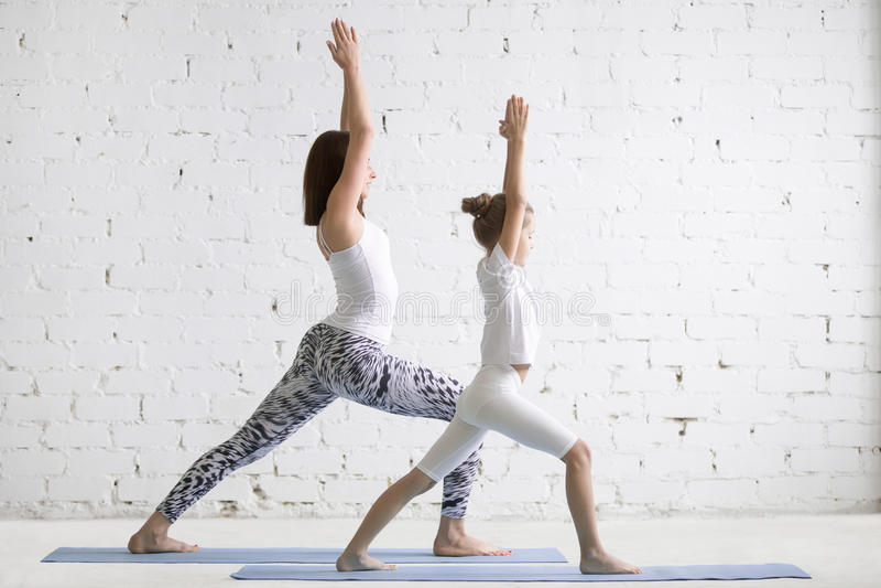 Formation des enseignants de yoga d'enfants avec l'enfant de fille une pose de Virabhadrasana images stock