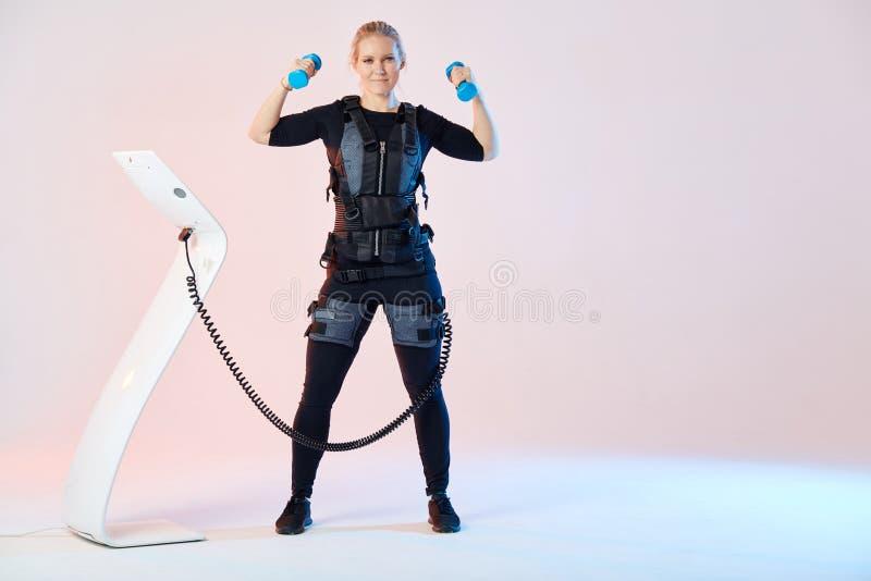 Formation forte gaie de fille avec la machine ?lectrique de stimulation de muscle images stock