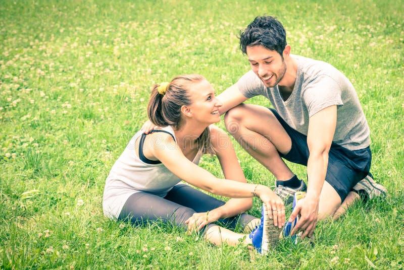 Formation heureuse de couples de forme physique et étirage en parc images stock