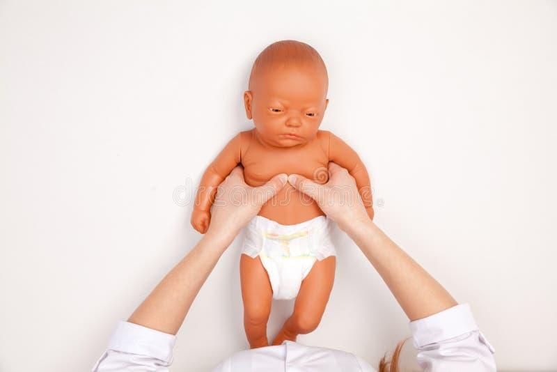 Formation infantile de premiers secours - docteur montrant la compresse manuelle de coffre photos stock