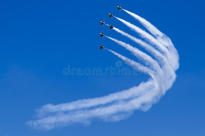Formation of jet aircrafts turns as a team in blue sky. stock photos